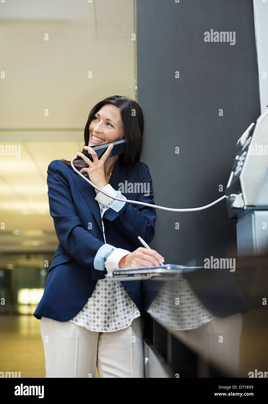 Businesswoman talking on pay phone outdoors - Stock Image