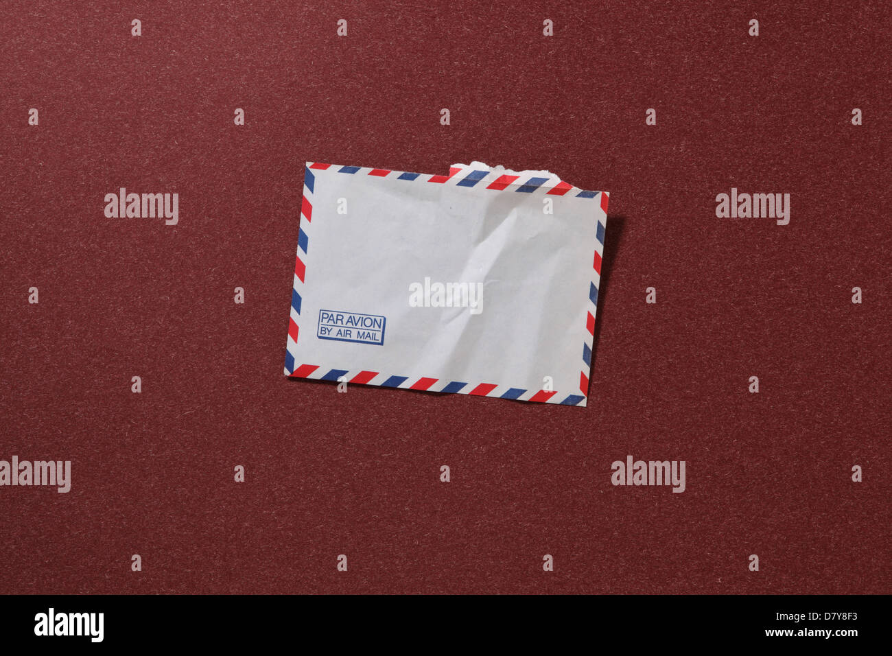 An air mail envelope slightly worn and torn. - Stock Image
