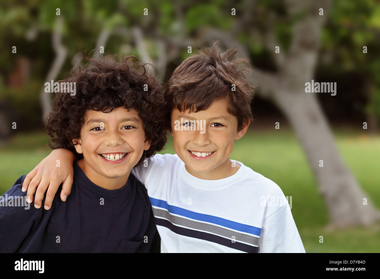 Two smiling happy young mixed race boys outside - Stock Image