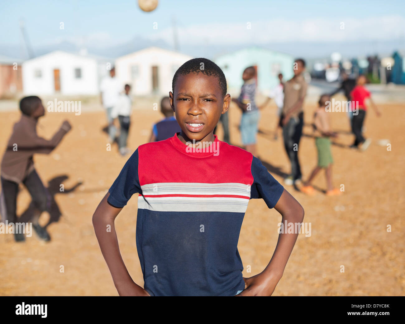 Boy standing in dirt field Stock Photo