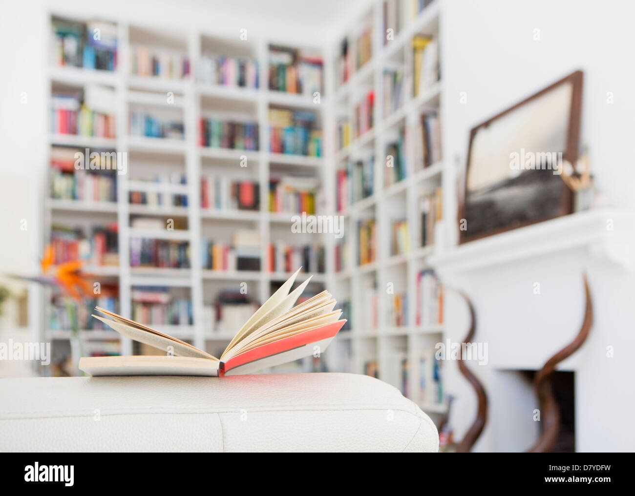 Open book on arm of sofa in living room - Stock Image