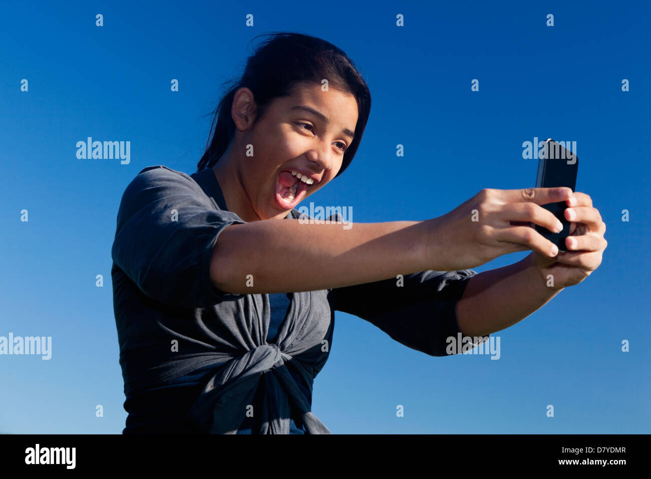Hispanic teenage girl taking picture Stock Photo