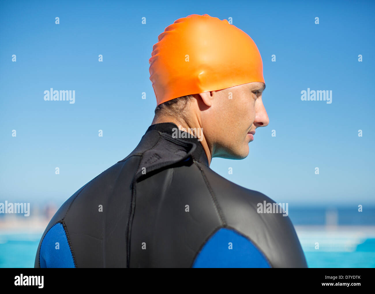 Triathlete wearing wetsuit and cap - Stock Image
