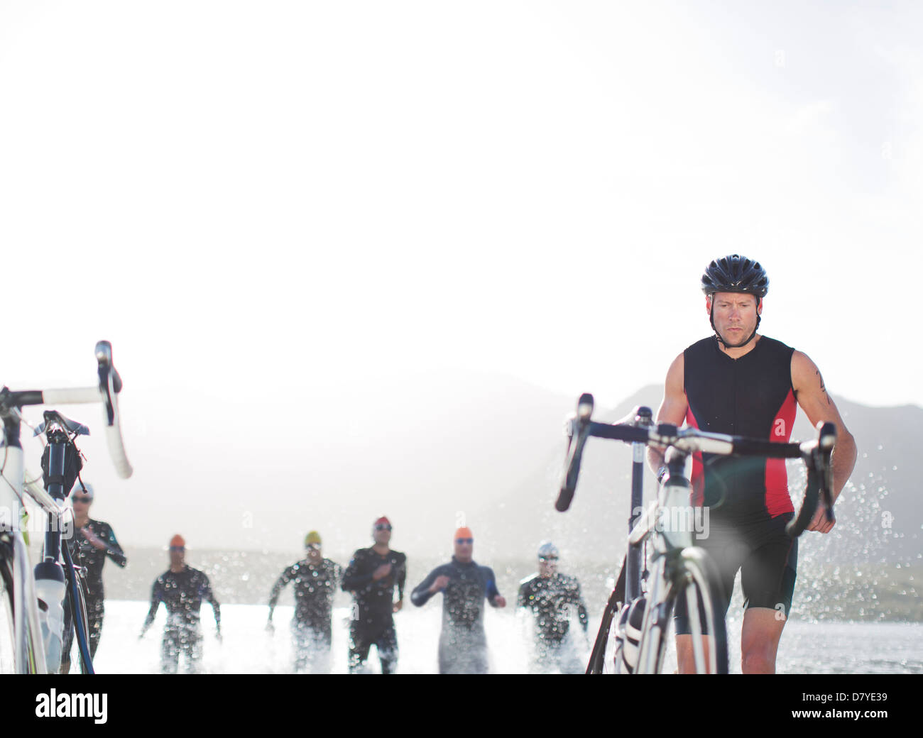 Triathletes emerging from water, - Stock Image
