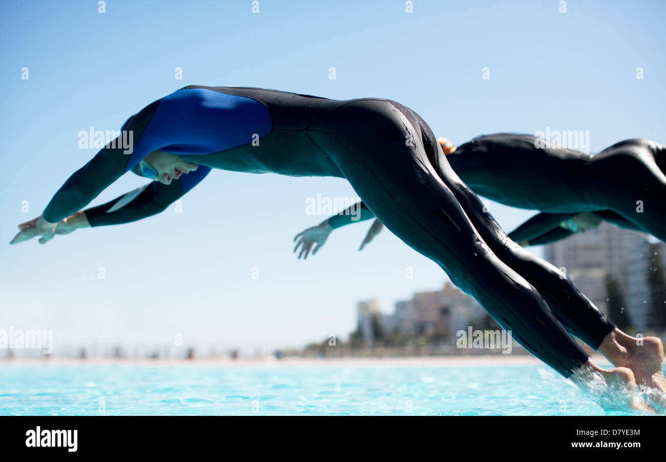 Triathletes diving into swimming pool - Stock Image