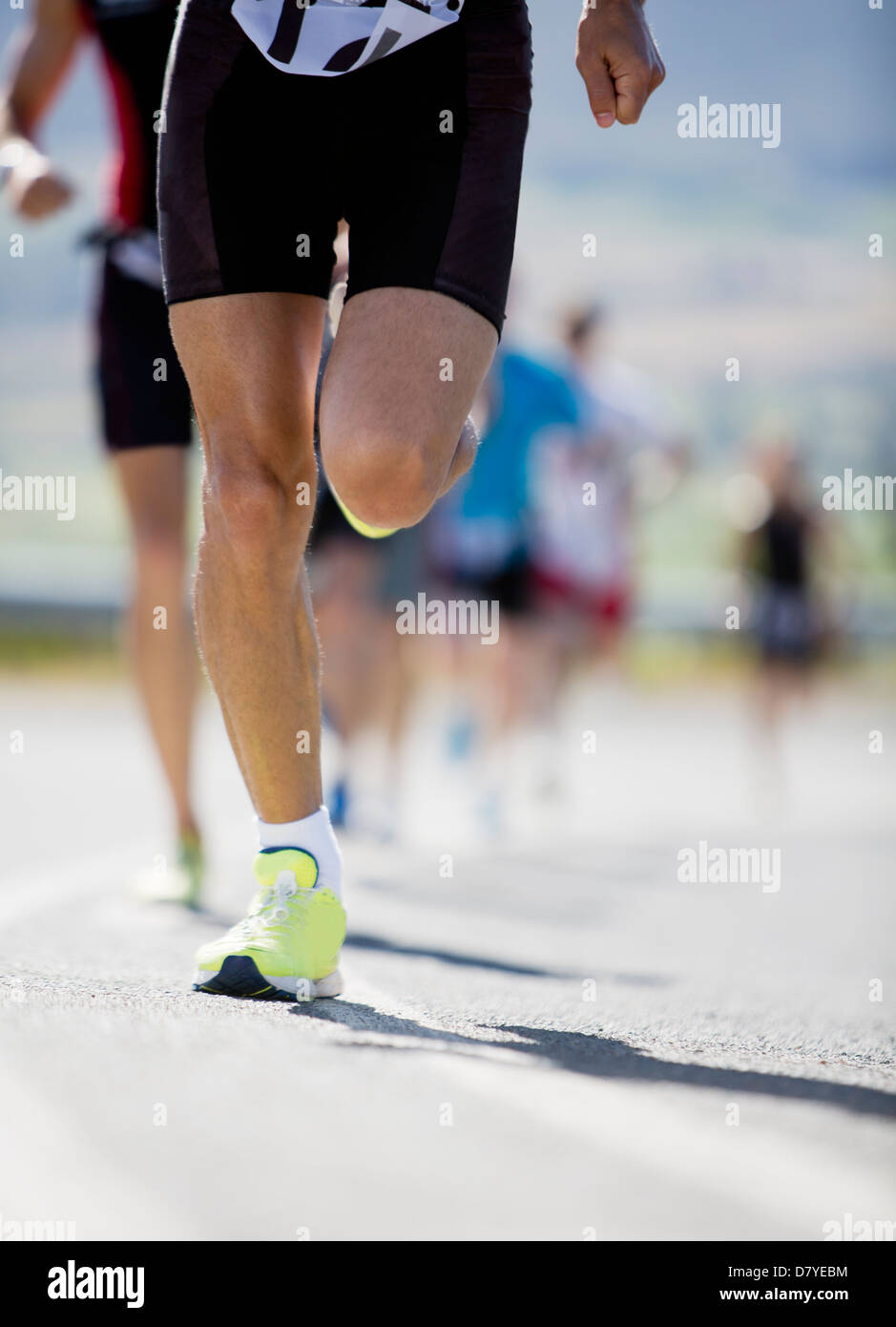 Runner in race on rural road - Stock Image