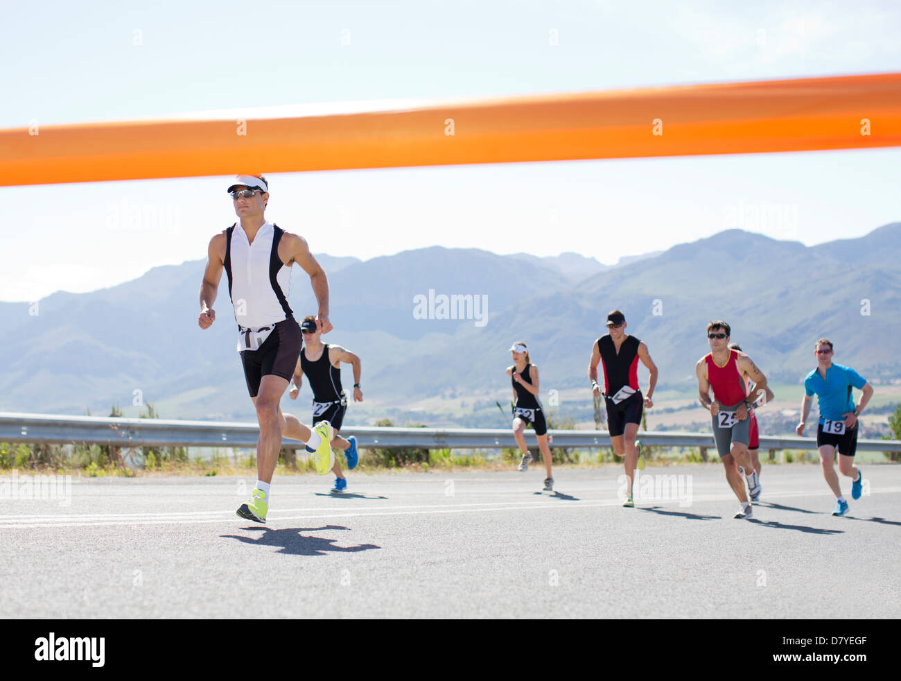 Runners crossing race finish line - Stock Image