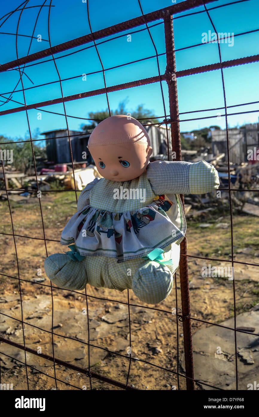 Photo of an abandoned doll on a junkyard fence - Stock Image