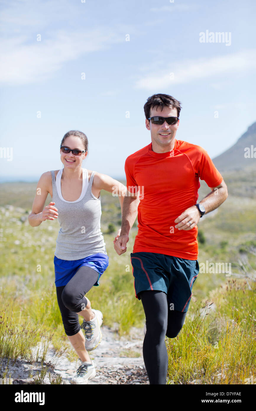 Couple running in rural landscape - Stock Image
