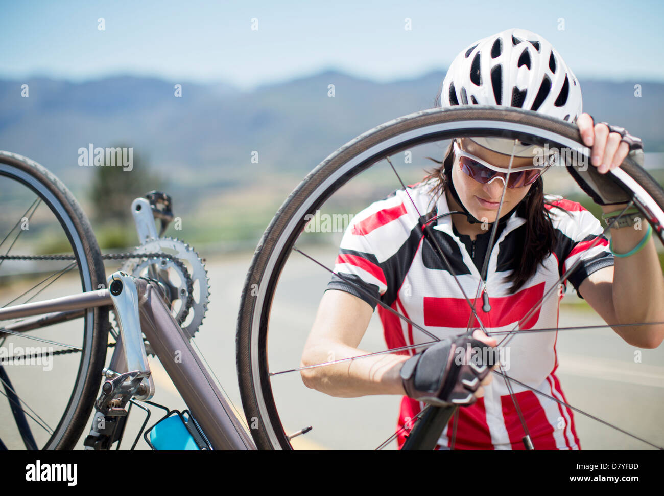 Cyclist adjusting tire on rural road - Stock Image