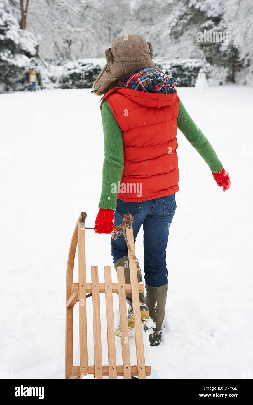 Woman pulling wooden sled in snow - Stock Image