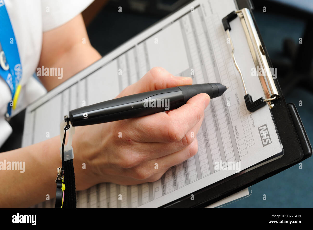 Nurse filling in an NHS form with a digital pen - Stock Image