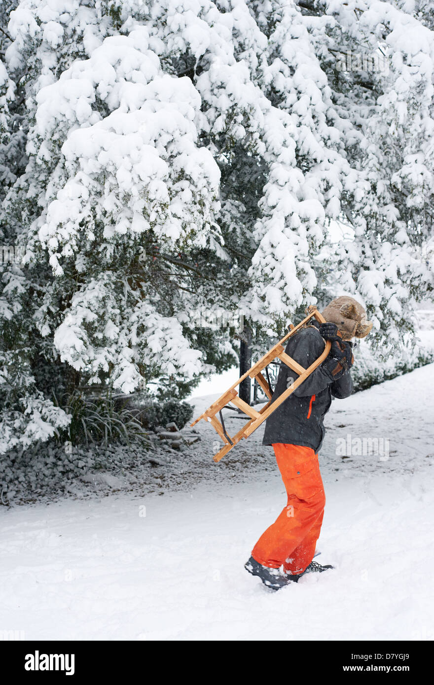 Boy carrying wooden sled in snow - Stock Image