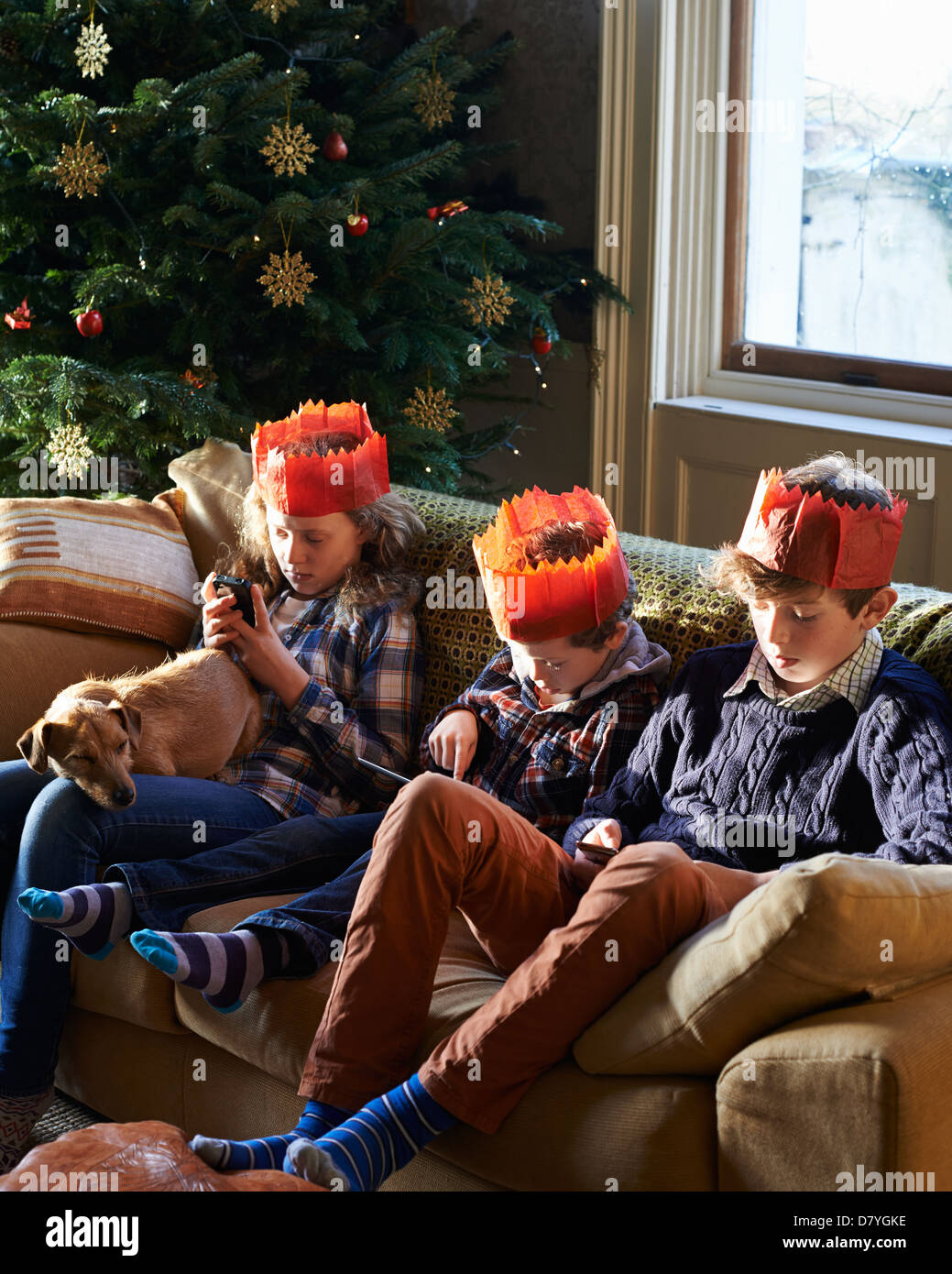 Children in paper crowns relaxing on sofa - Stock Image