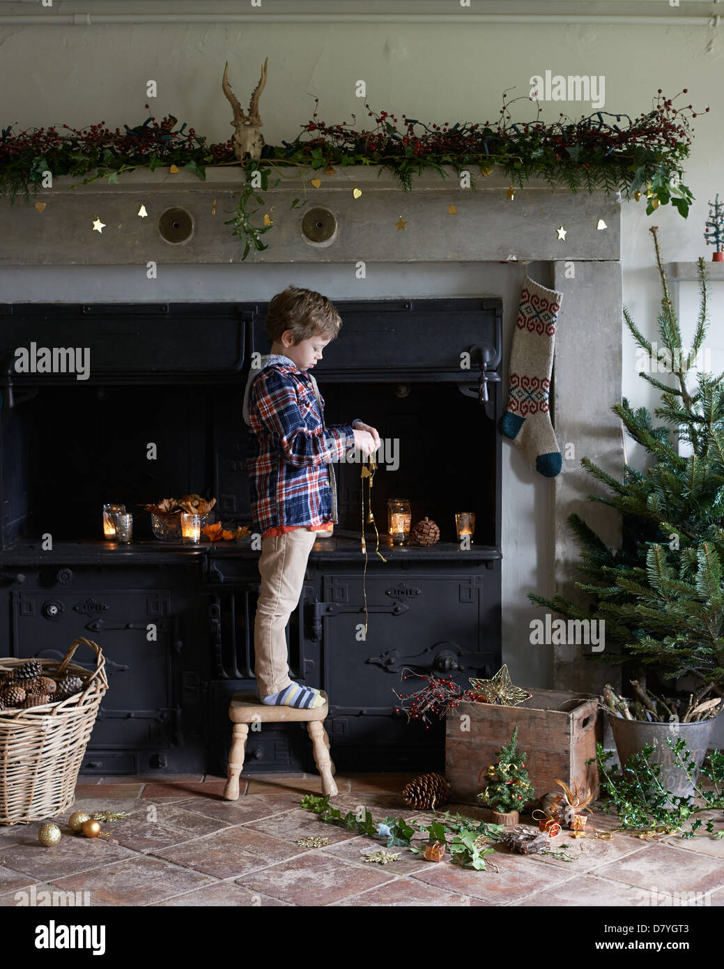 Boy decorating Christmas fireplace - Stock Image