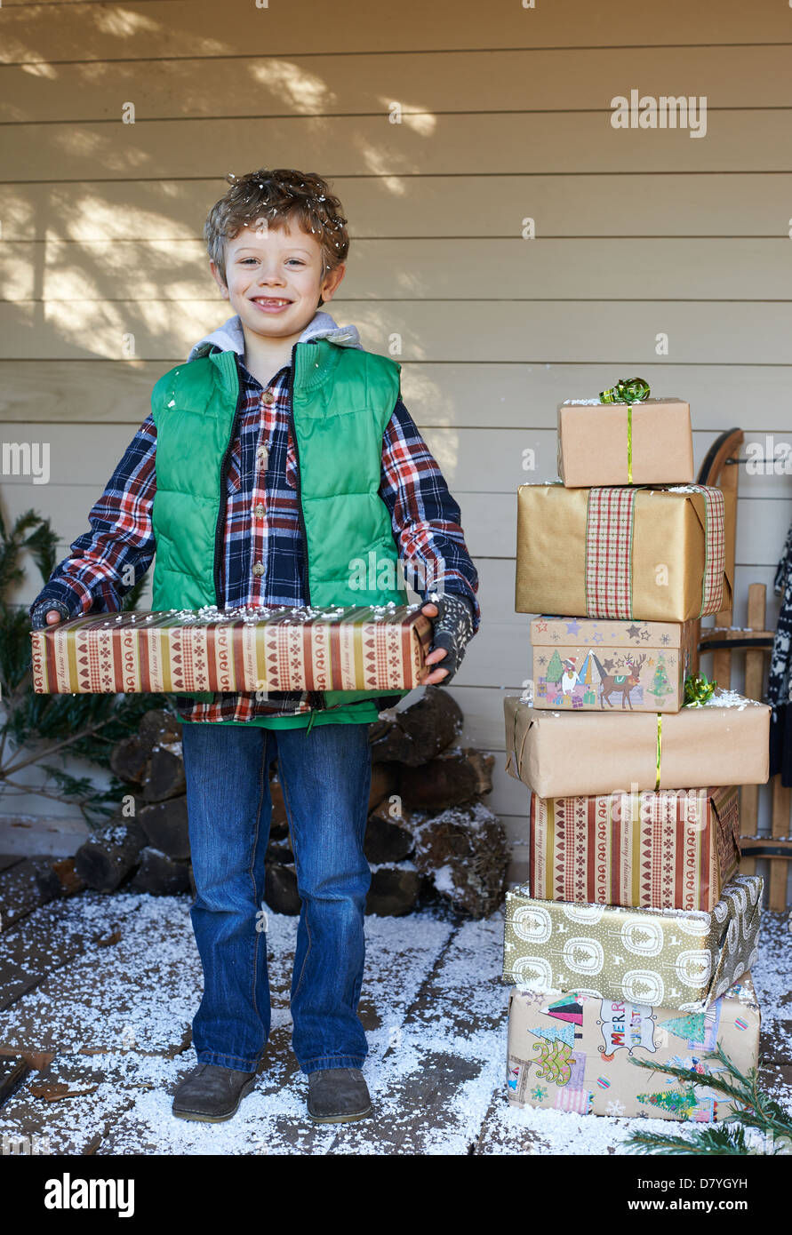 Boy holding Christmas gifts on snowy porch - Stock Image