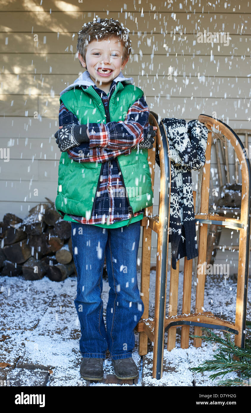 Boy with wooden sled in snow - Stock Image
