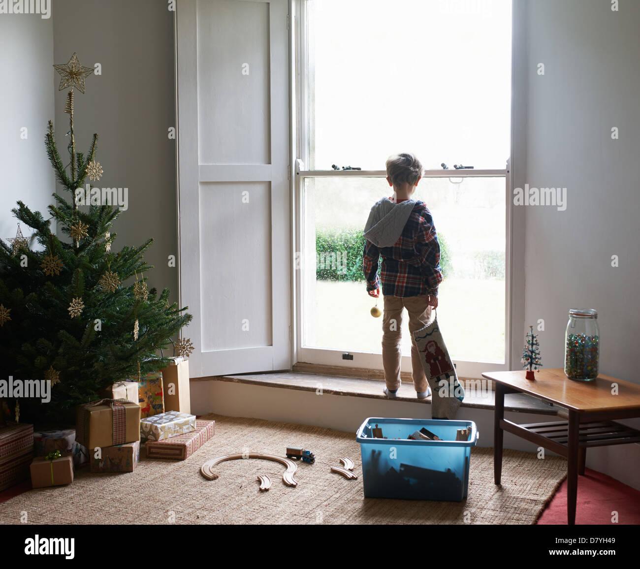 Boy holding Christmas stocking at window - Stock Image