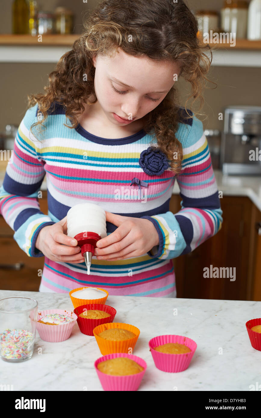Girl decorating cupcakes in kitchen - Stock Image