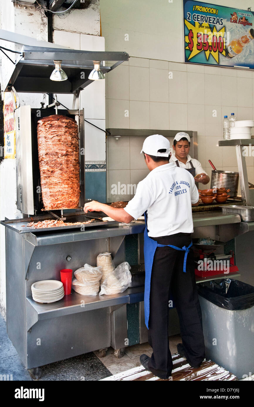 2 young Mexican men workers at stainless steel counter in fast food restaurant make tacos al pastor from meat roasting - Stock Image
