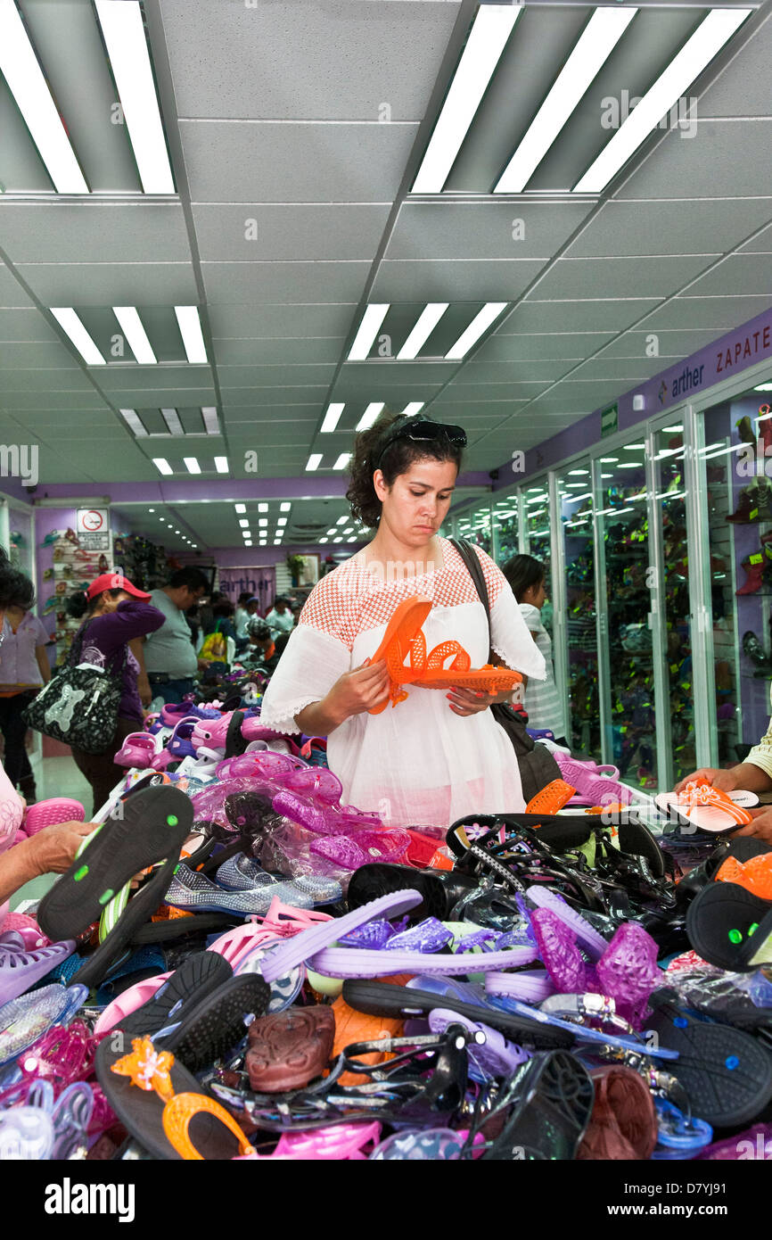 looking for bargain in outlet store, woman selects orange pair from large heap colorful colourful jellybean shoes - Stock Image