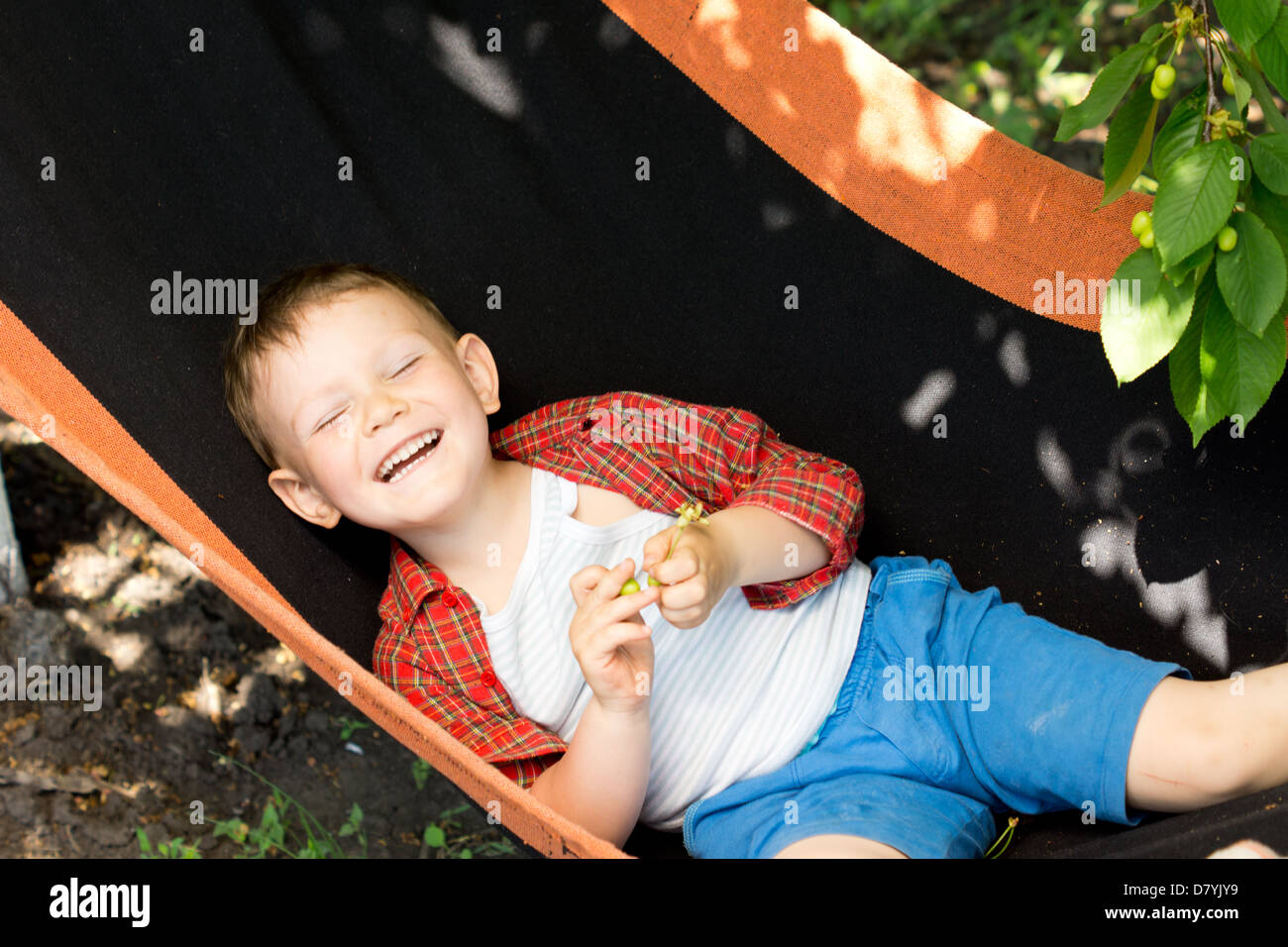 Laughing little boy lying on his back in a hammock under a shady tree enjoying the sunny spring weather Stock Photo