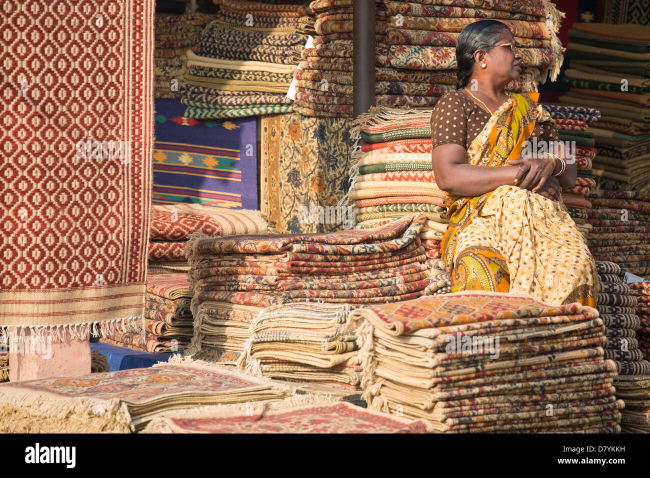 Woman selling carpets at Dili Haat in Delhi, India - Stock Image