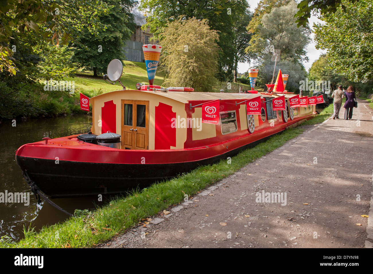 Colourful traditional barge boat moored on sunny summer day (floating shop selling ice creams) - scenic Leeds Liverpool - Stock Image