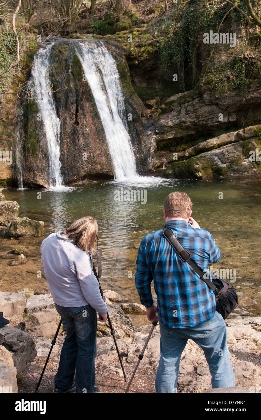 Rear view of 2 photographers using tripods (man & woman) taking photos of scenic waterfall - Janet's Foss, - Stock Image