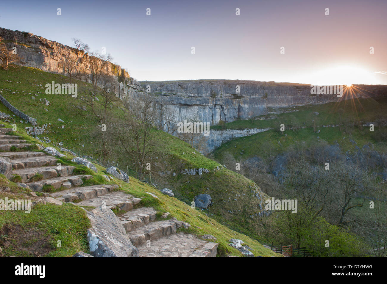 Scenic view of dramatic Malham Cove at sunset with sunburst over huge, sheer, curving limestone cliff in beautiful - Stock Image