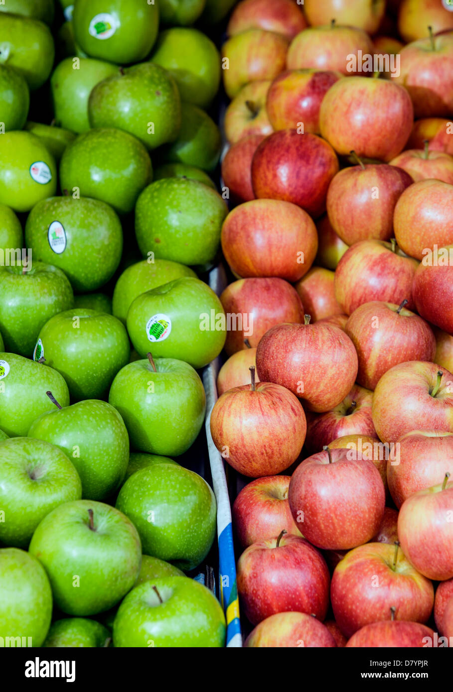 Green and red apples on a market stall. - Stock Image