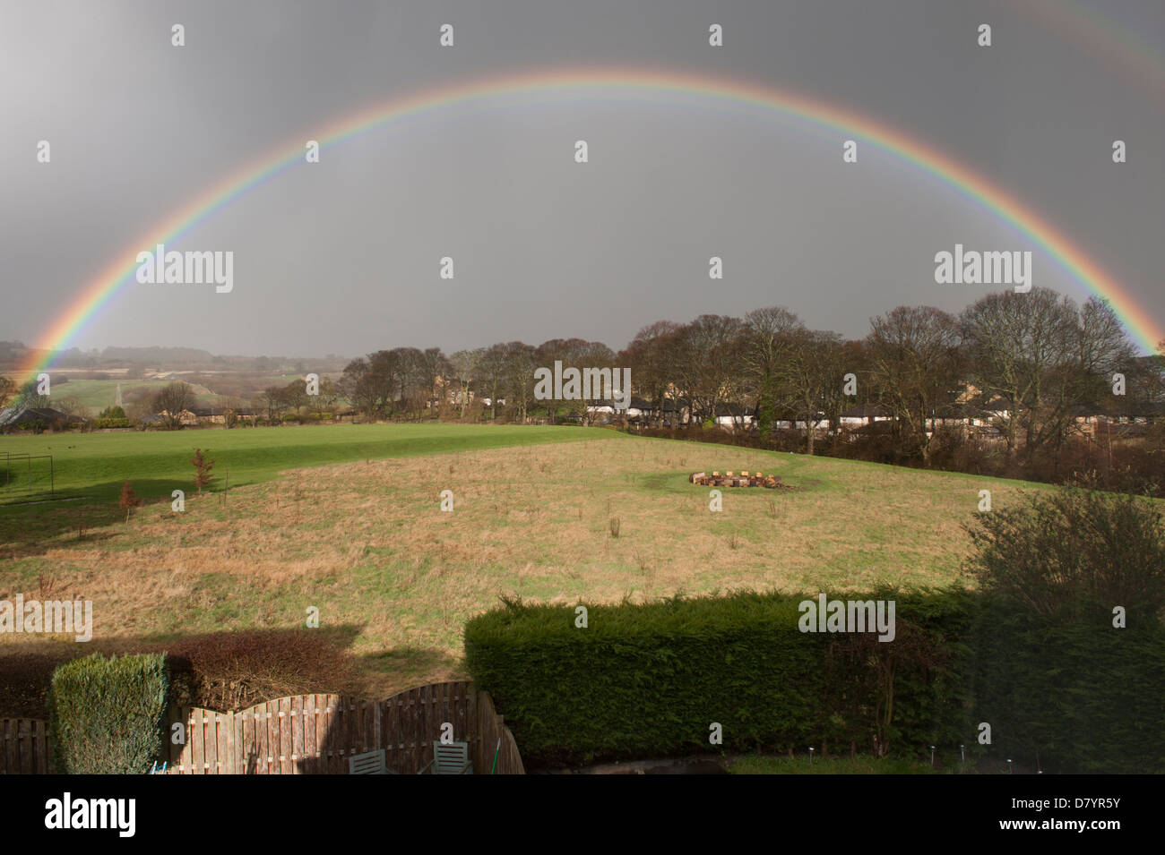 Beautiful rainbow creating a perfect arch across grey rainclouds in sky, over fields in sea-rural landscape - Baildon, Stock Photo