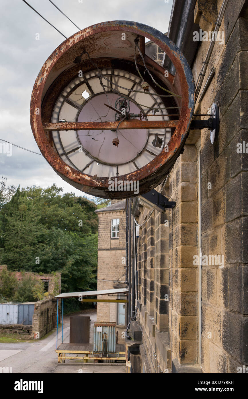 Close-up of large broken rusty clock fixed to wall at Greenholme Mills, a partially derelict Victorian worsted mill - Stock Image