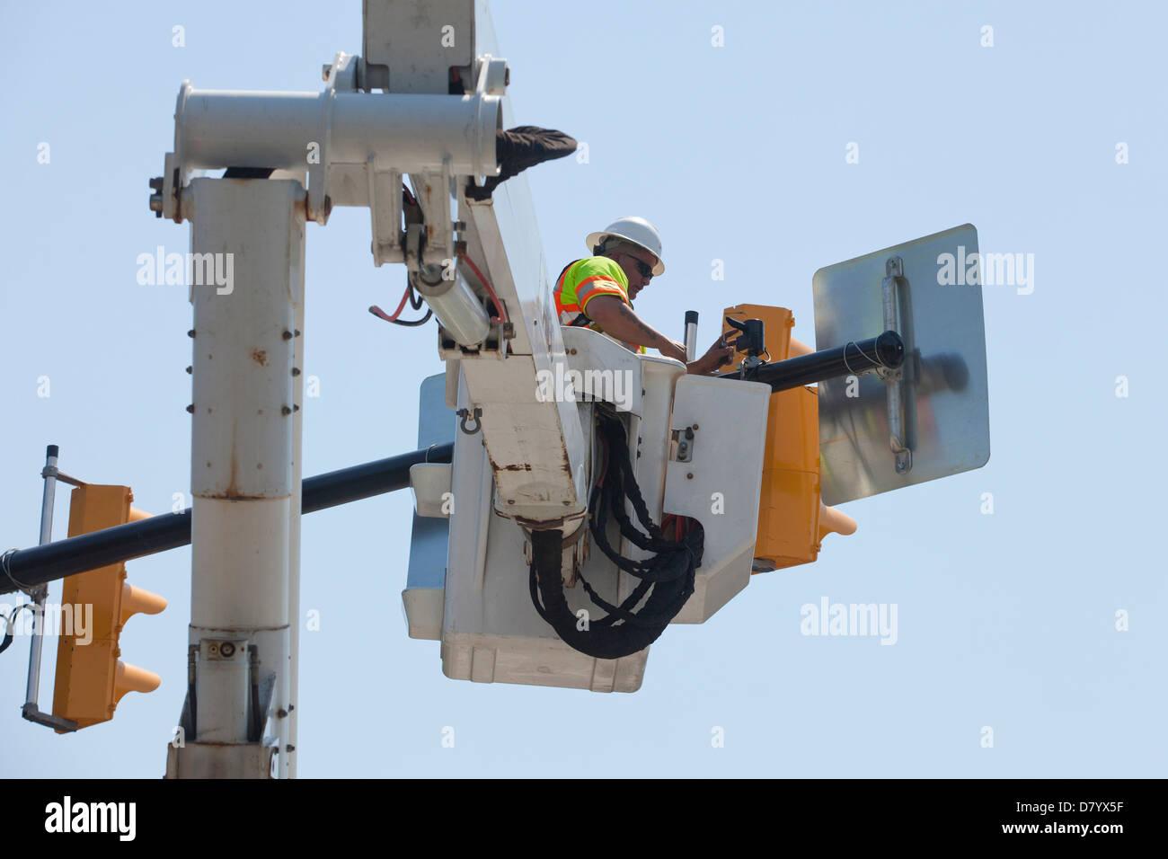 Workman installing new traffic lights - Stock Image