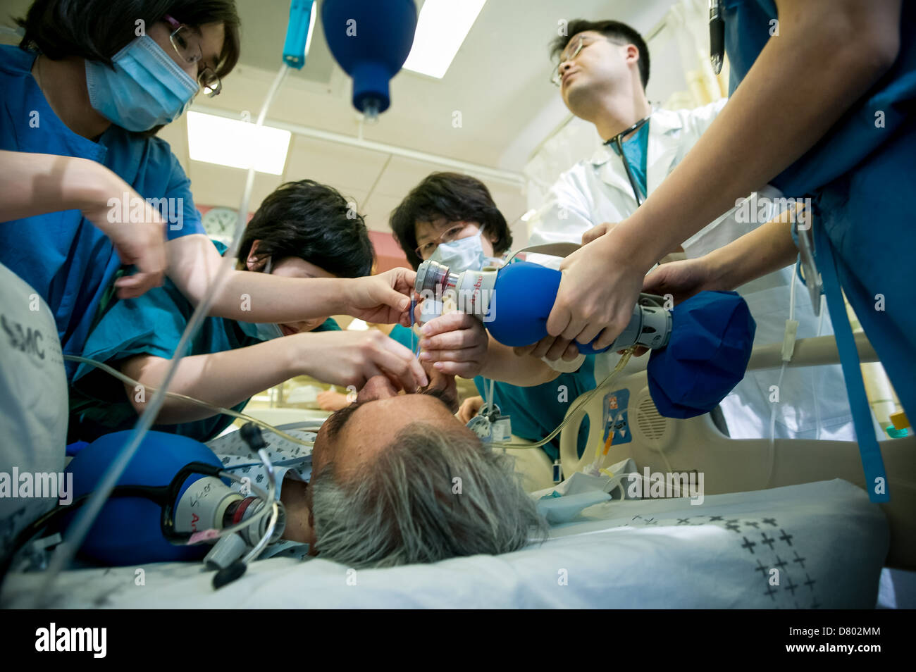 Medical staff use an oxygen tank to help revive the patient who has been under anaesthetic at the intensive care Stock Photo