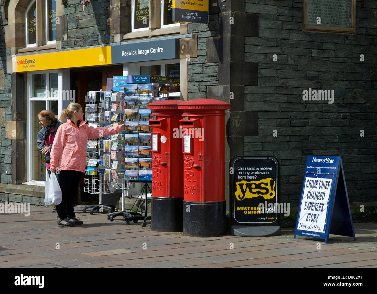 Woman browsing through postcards outside the post office, Keswick, Lake District National Park, Cumbria, England - Stock Image