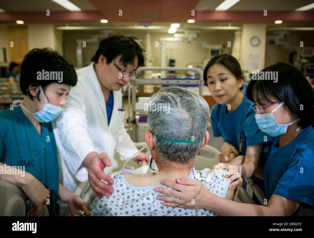 Medical staff help an intensive care patient to sit up, the Samsung Medical Center, South Korea. - Stock Image