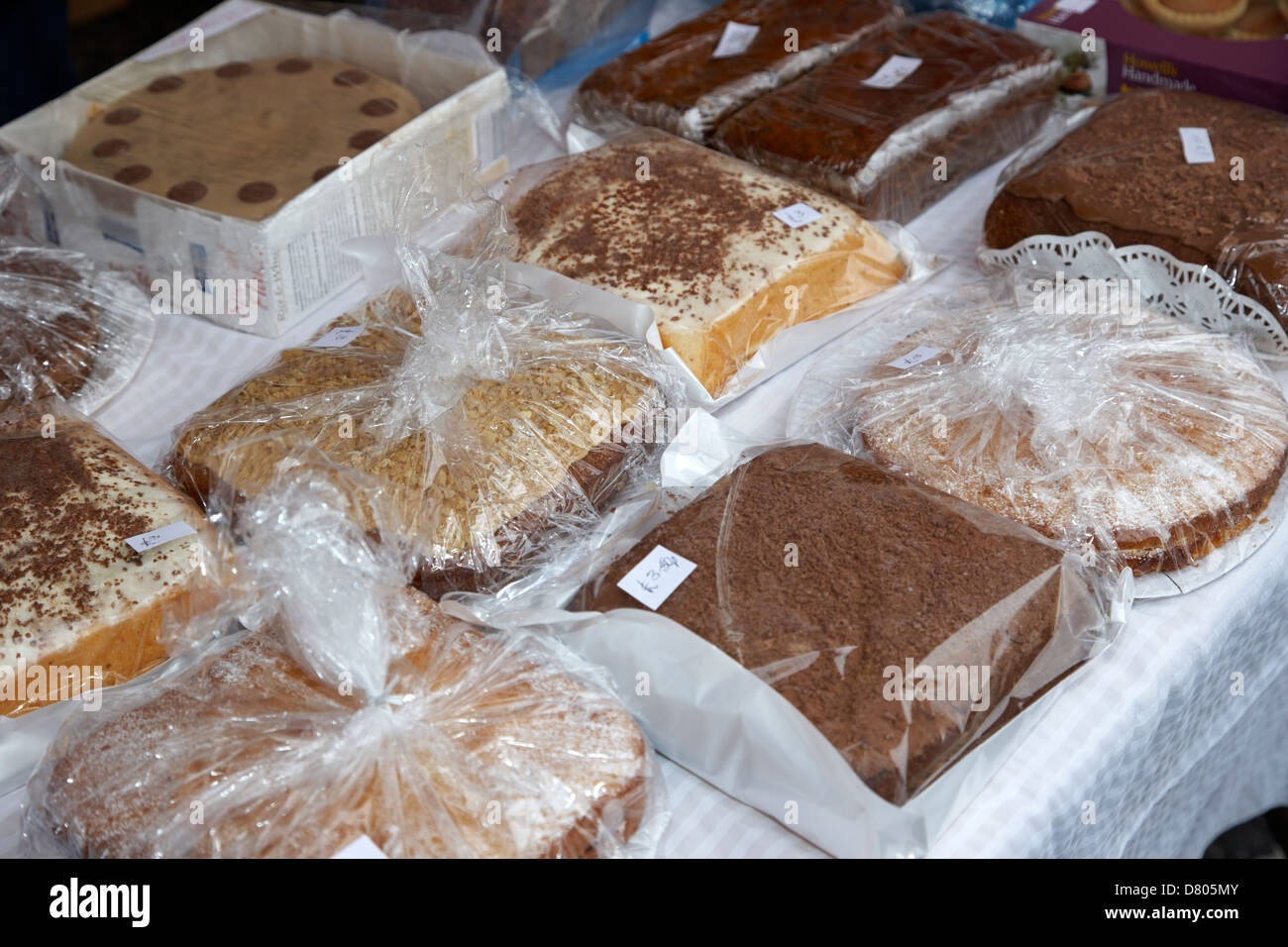 home made cakes on a charity stall at an outdoor event in the uk - Stock Image