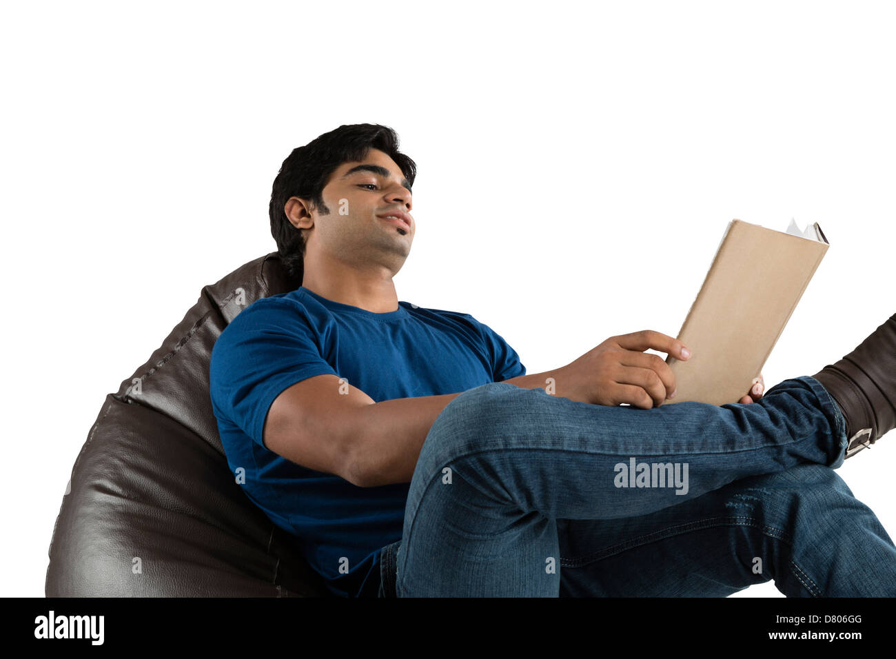 Man sitting on a bean bag and reading a book - Stock Image