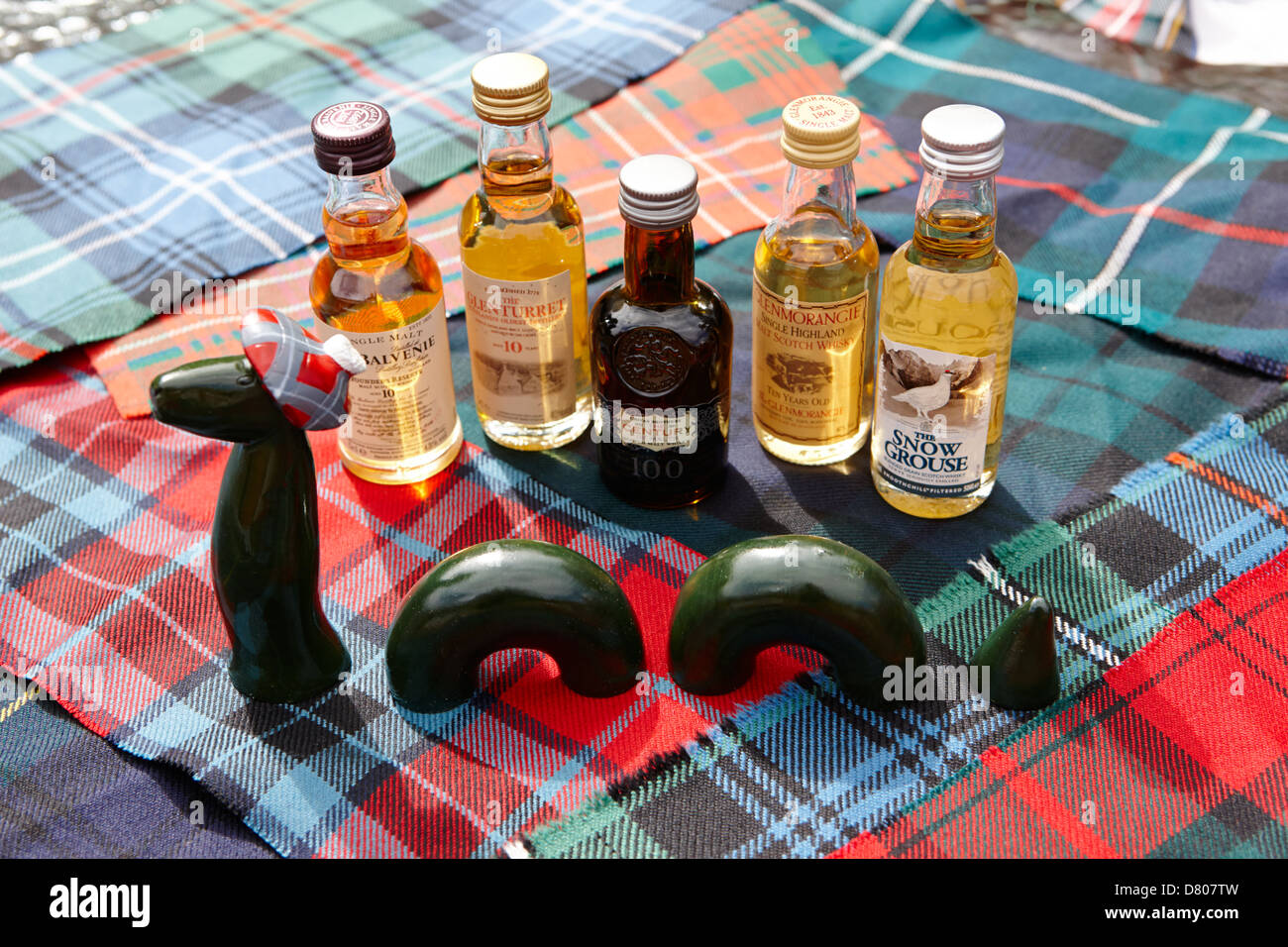 tourist model of the loch ness monster and a range of scotch whiskies on traditional scottish clan tartans - Stock Image