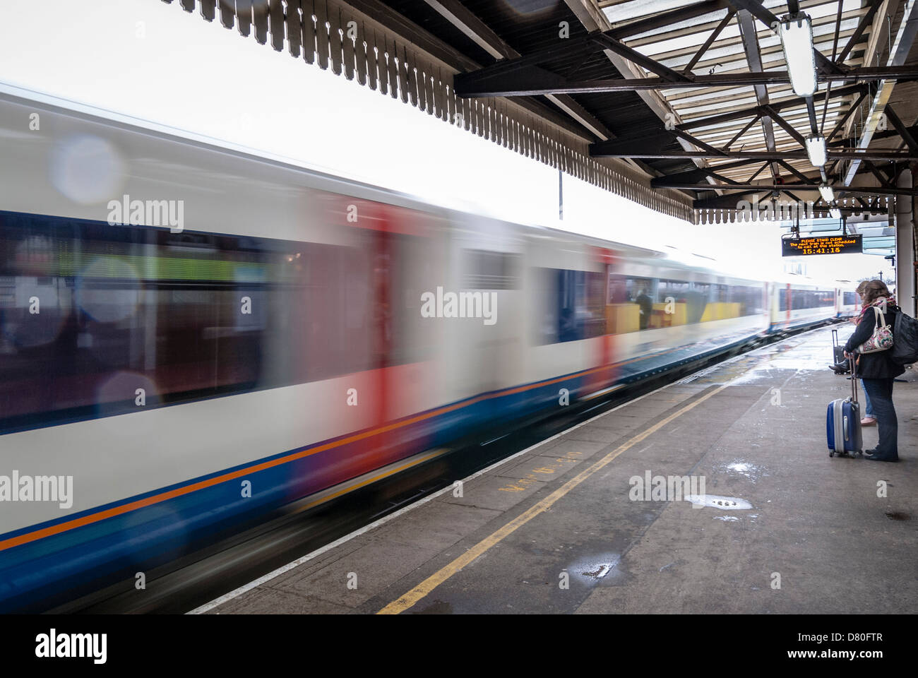 Passengers standing back from non stopping train at Clapham Junction - Stock Image