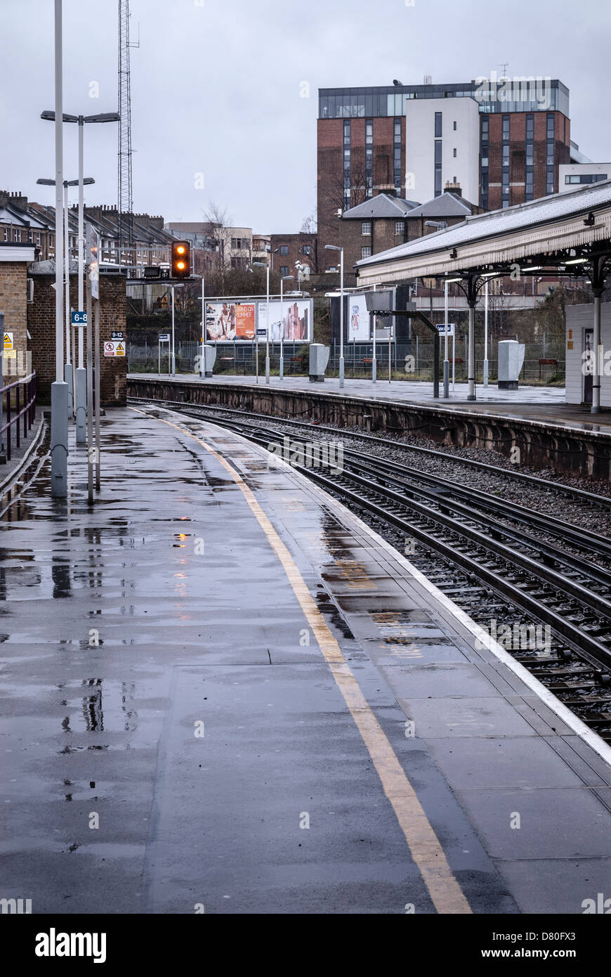 deserted clapham junction platforms and railway tracks in the rain - Stock Image