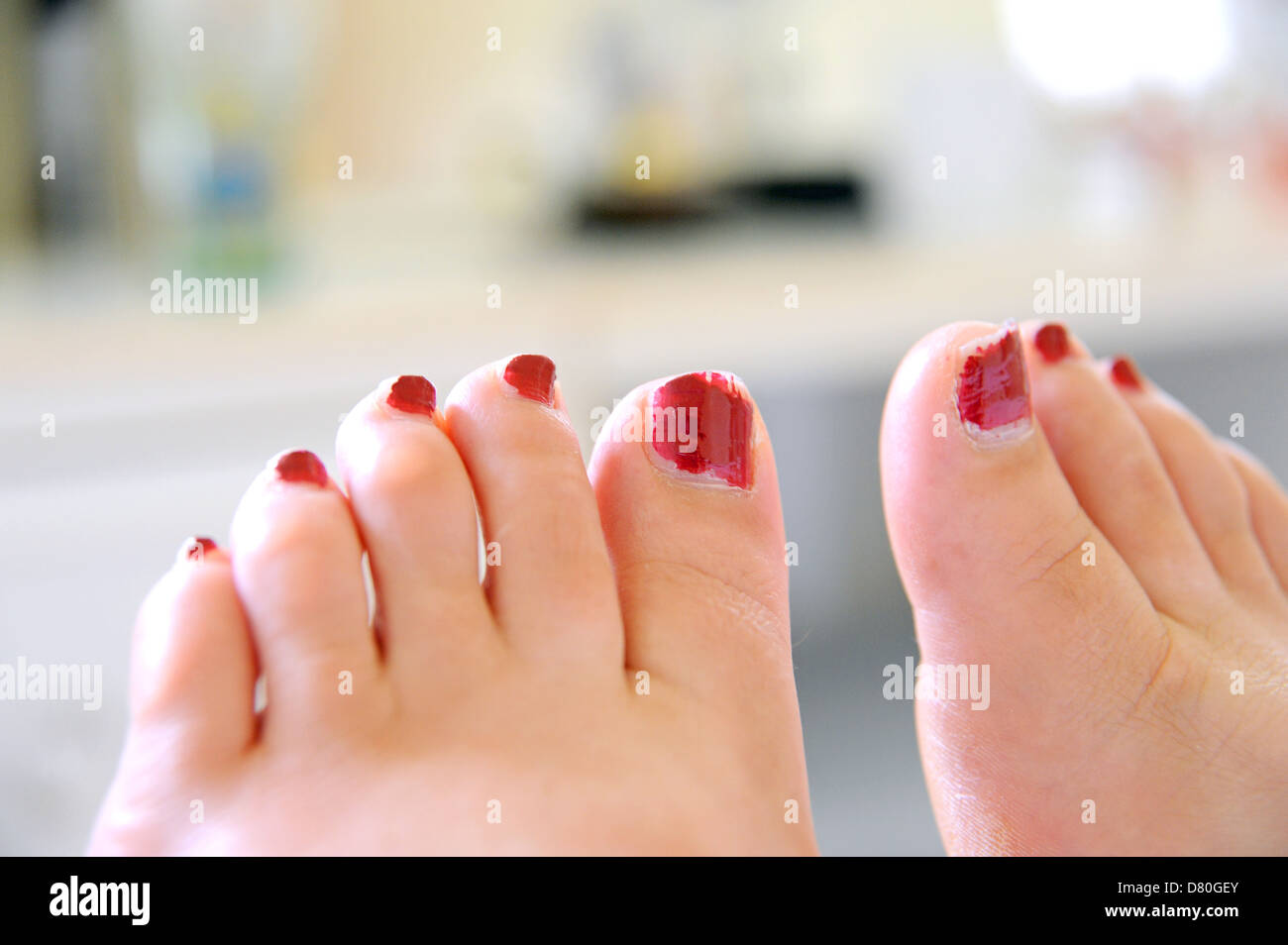 Female feet with red painted toe nails sticking out of the end of ...