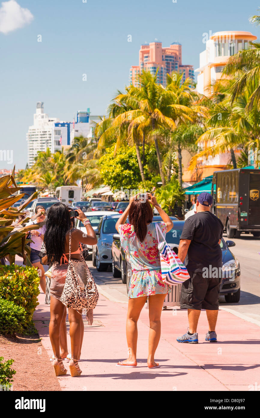Female African-American tourists taking pictures at the Art Deco District in Miami Beach, Florida, USA - Stock Image