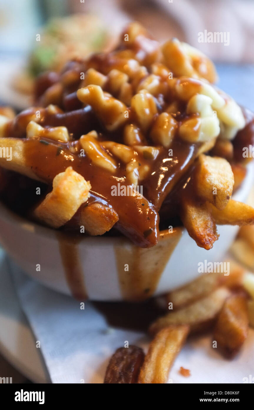 Poutine is a fast food dish that originated in Quebec and can now be found across Canada. - Stock Image