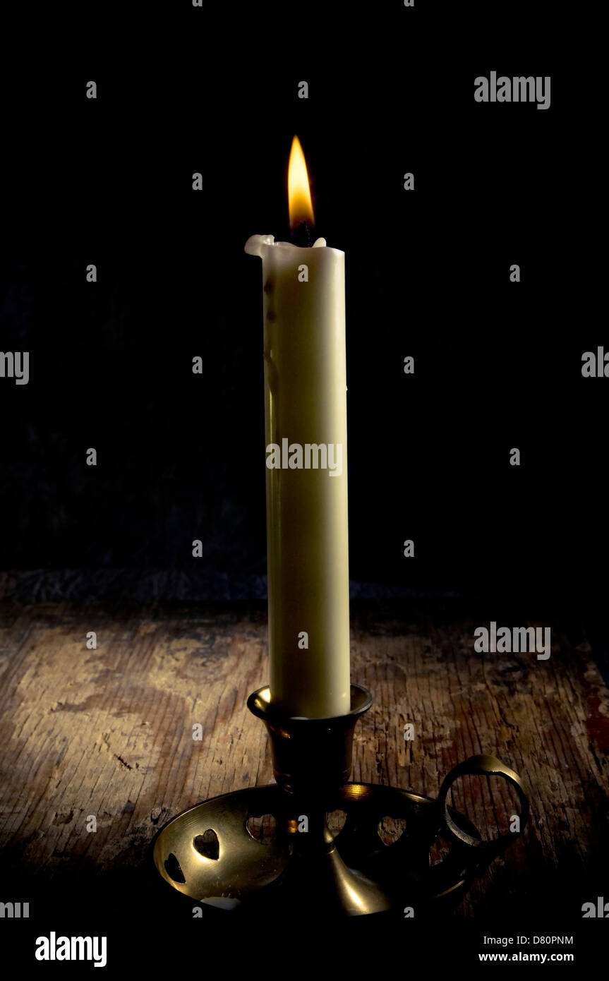 a candle in an old candlestick - Stock Image