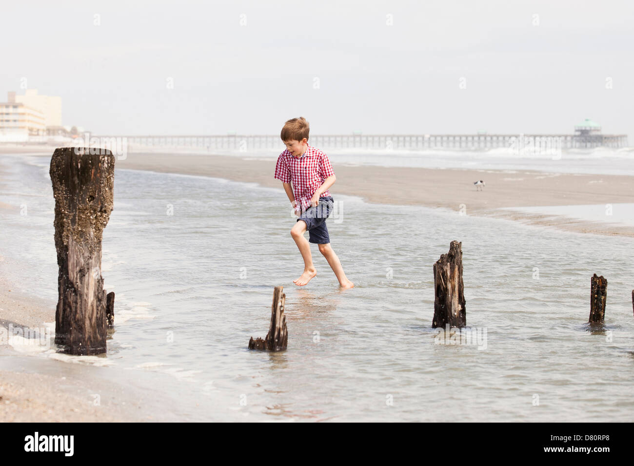 boy walking through tide - Stock Image