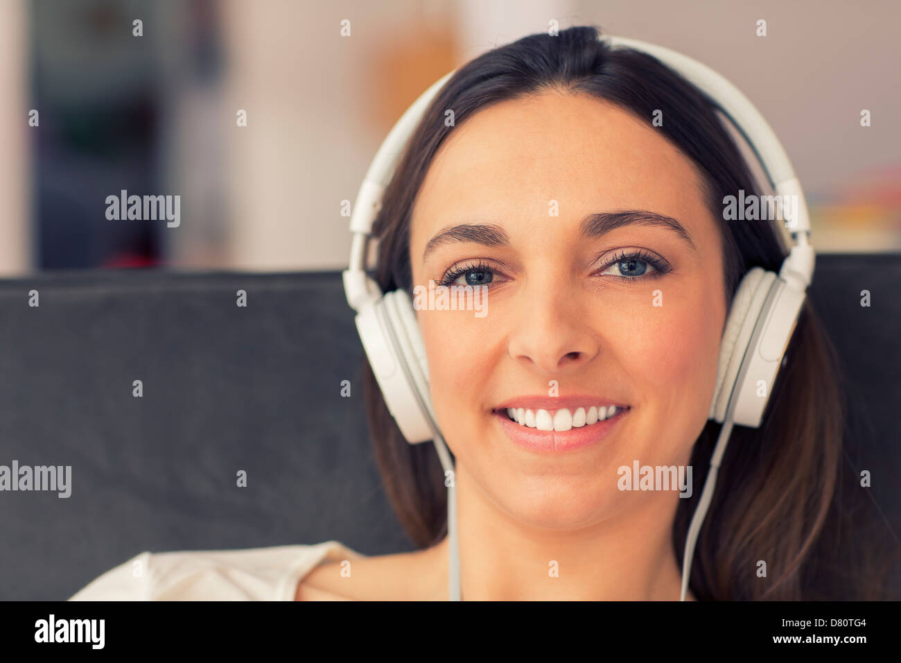 Portrait of simling woman whit her headphones. she listens to music - Stock Image