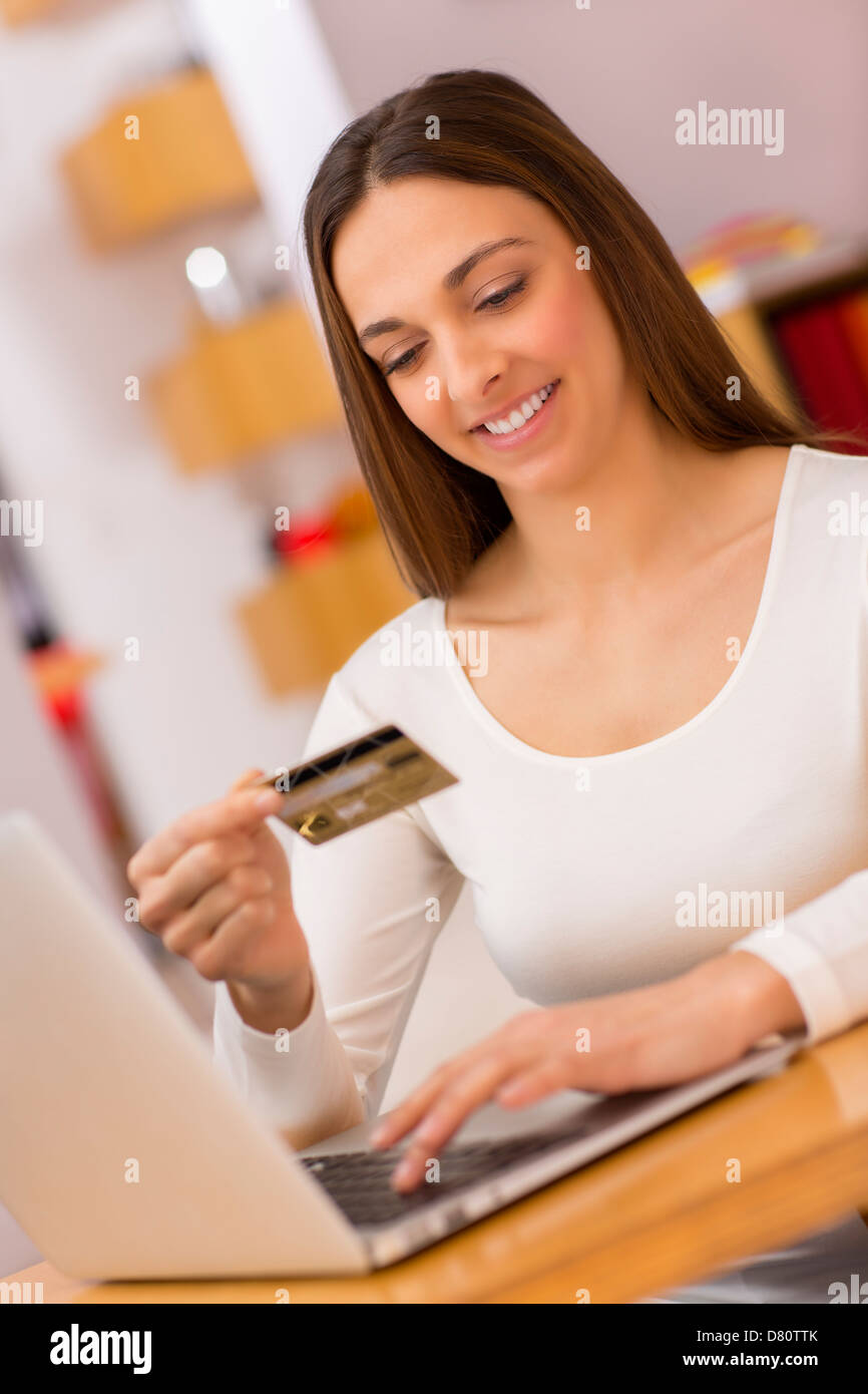 Female holding a charge card and shopping from the web on laptop Stock Photo