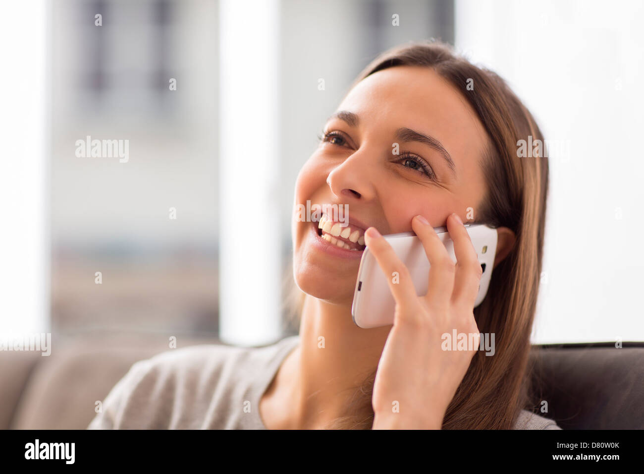 Pretty young female using white mobile phone at home smiling - Stock Image